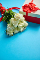 Bouquet of white roses with red bow on blue background. Boxed gift on side