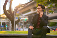 Hispanic businessman thinking while talking on phone with nature in city