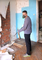 repair in the home. A young man knocks down old Soviet-era plasterboard slabs from the wall with iro
