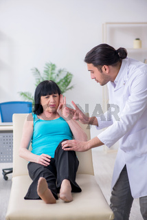 Young male doctor examining old female patient