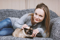 happy young woman relaxing on sofa with cat