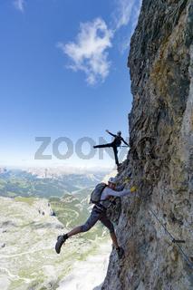 attractive female climbers on a steep Via Ferrata in the Italian Dolomites and having fun
