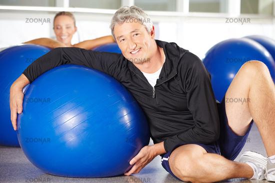 Älterer Mann mit Gymnastikball im Fitnesscenter