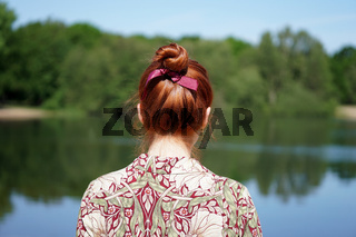 back view of woman with red hair bun looking at lake