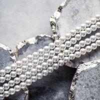 Pearl jewellery on marble, luxury background