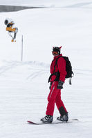 Snowboarder in red on snowy ski slope