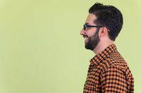 Closeup profile view of happy young bearded Persian hipster man smiling