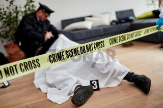 Polizist neben Leiche nach Mord am Tatort