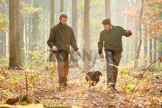 Zwei Jäger mit einer Bracke auf Treibjagd im Wald