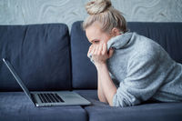 Scaried blond woman lying prone on sofa and looking on laptop computer screen