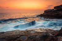Stunning sunrise and waves crash over rocks on the Sydney sea coast