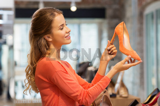 happy young woman choosing shoes at store