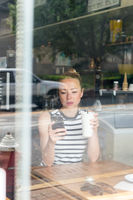 Thoughtful woman reading news on mobile phone during rest in coffee shop.