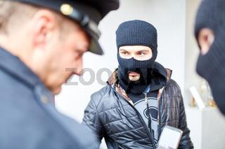 Polizist oder Wachmann kontrolliert zwei Einbrecher