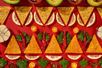 Ingredients of Guacamole dressing for mexican corn chips -chilly pepper, lemon slices, garlic, tomatoes, parsley green as a traditional pattern on a red background. Top view.