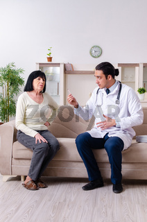 Young doctor examining senior old woman
