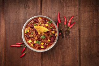 Chili con carne, a Mexican stew with red beans, cilantro, ground beef, and chili peppers, shot from the top with a nacho chip on a dark rustic wooden background