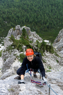 woman in her twenties climbing a steep Via Ferrata in the Dolomites of Alta Badia
