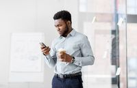 businessman with smartphone and coffee at office