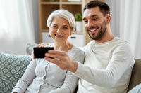 senior mother with adult son taking selfie at home