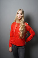 young woman with long blond hair standing against gray wall
