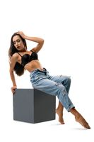Girl in black bra and jeans on cube isolated shot