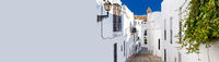 Horizontal cropped image with white copy space wall narrow street of Vejer de la Frontera spanish picturesque village, popular hilltop town municipality in province of Cadiz, Costa de la Luz, Spain