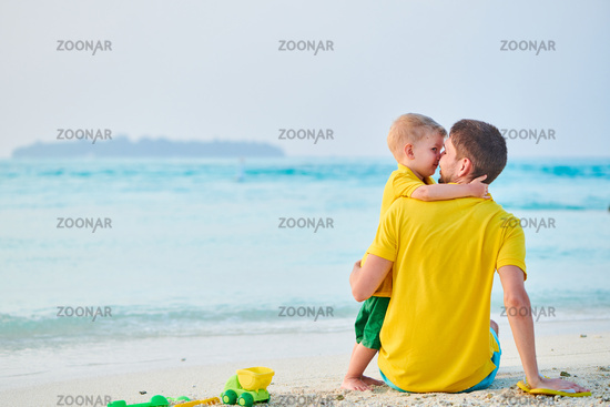 Toddler boy on beach with father
