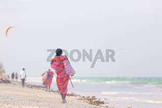 Rear view of traditonaly dressed maasai man selling hand made jewelry on picture perfect tropical Paje beach, Zanzibar, Tanzania, East Africa.