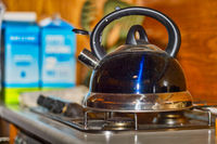 A whistling kettle stands on a switched off gas stove.