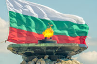 Eternal fire burns against the backdrop of the National Flag of Bulgaria. The Shipka Freedom Monumen