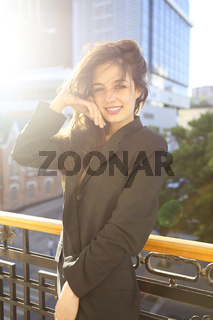 Young woman in jacket standing on balcony with city background at sunset
