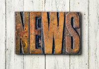 Antique letterpress wood type printing blocks on a white backgound - News