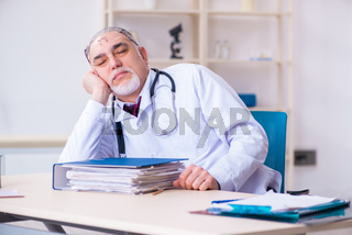 Old male doctor working in the clinic