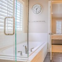 Square Bathroom interior with built in bathtub shower stall and vanity area