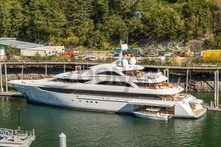 September 14, 2018 - Juneau, Alaska: Sleek white Luxury yacht docked in city harbor.