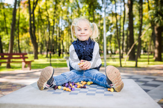 Funny Caucasian baby girl blonde does not want learn, does not want to school, want to play, laugh and indulge. child with hair ponytail sits table legs forward, spread out, mess, tabletop logic game