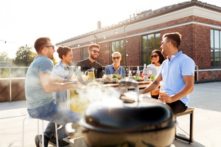 happy friends at barbecue party on rooftop