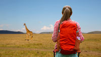 woman with backpack over african savannah