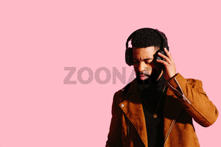 Portrait of a cool man with beard touching his headphones listening to music, isolated on pink studio background