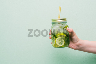 Summer refreshing cocktail in the hands of the girl. Cold drink mojito, with a striped tubule. Fruit non-alcoholic or alcoholic beverage in a glass jar
