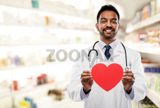 smiling indian male doctor with red heart shape