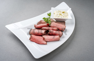 Traditional lunch meat with sliced cold cuts roast beef and remoulade as closeup on a white plate with copy space