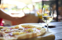 Pizza and white wine in outdoor restaurant.