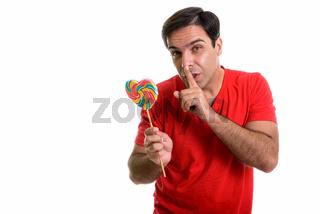 Studio shot of young Persian man holding heart shaped lollipop w