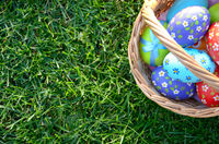 Flat lay shot of Easter eggs in the wicker basket on green spring grass. Space for text