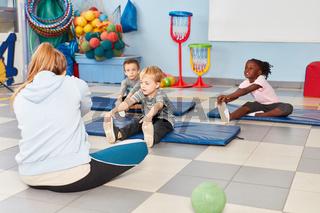 Gruppe Kinder macht Übung zum Dehnen