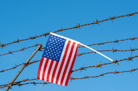 American flag on barbed wire fence