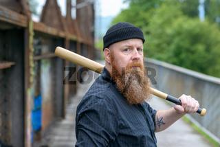 Hefty muscular bearded man with a baseball bat