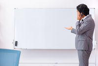 Young handsome businessman standing in front of whiteboard